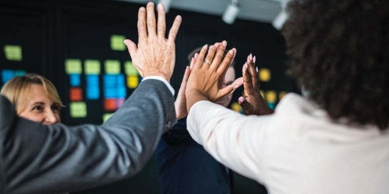 Business people give high fives